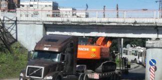 В Новокузнецке экскаватор на трейлере застрял под мостом